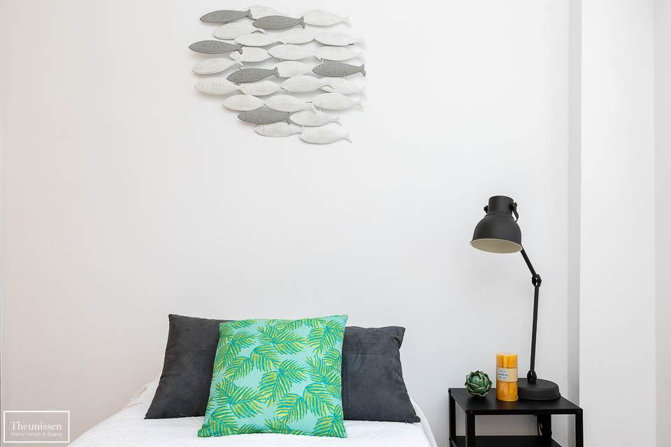 Decoración de dormitorio juvenil con mesilla de noche en negro y cojines en tonos grises y verdes.
